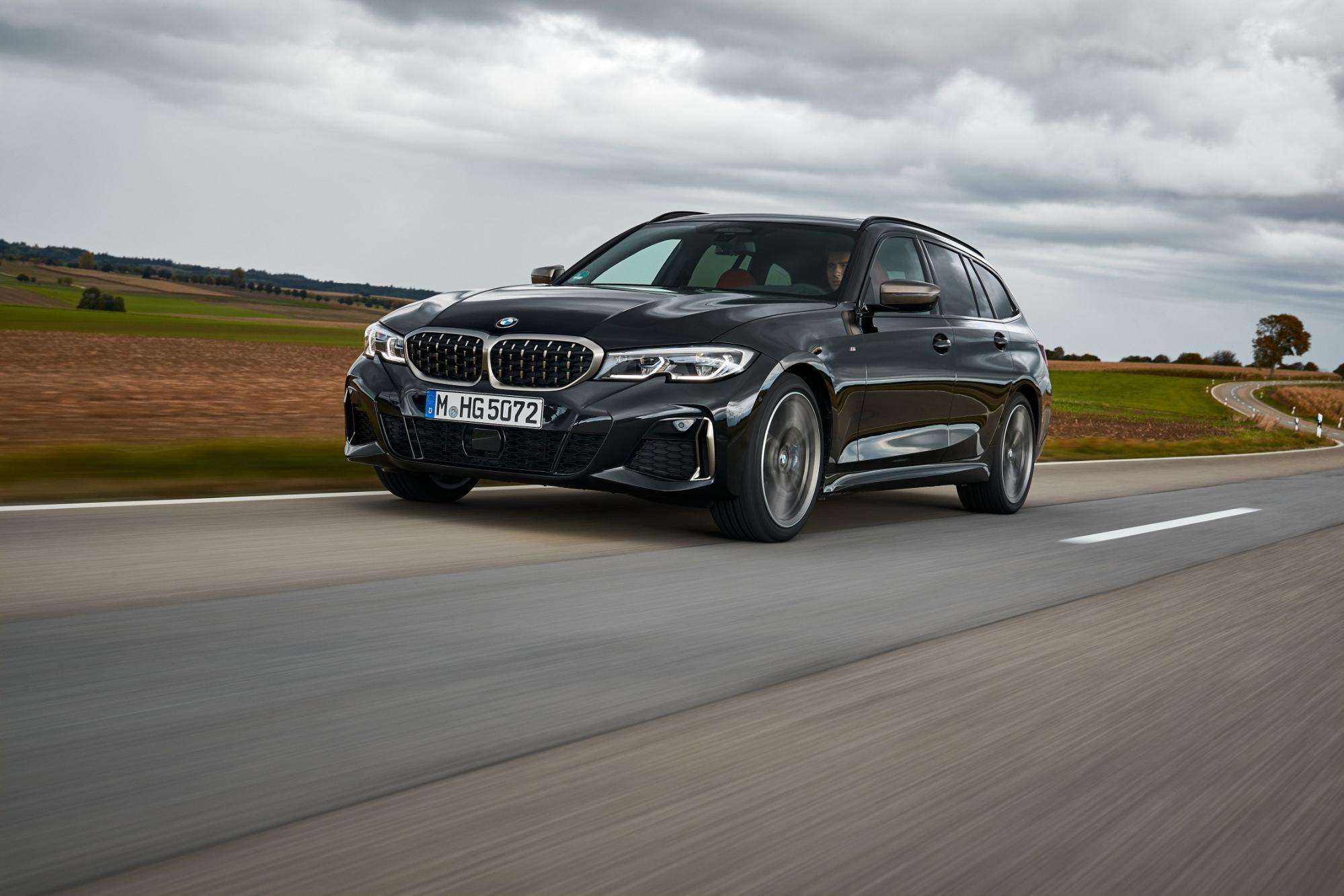田舎道を走行する黒の新型BMW3シリーズ ツーリング